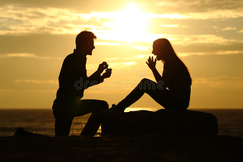 A proposta na praia com um homem que pede casa-se no por do sol imagens de stock royalty free