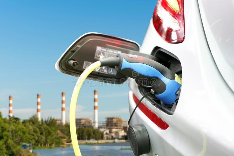 Propp av elektrisk tillförsel för maktkabel under uppladdning på det elektriska medlet för evbil som laddar på elkraftväxten med  arkivbild