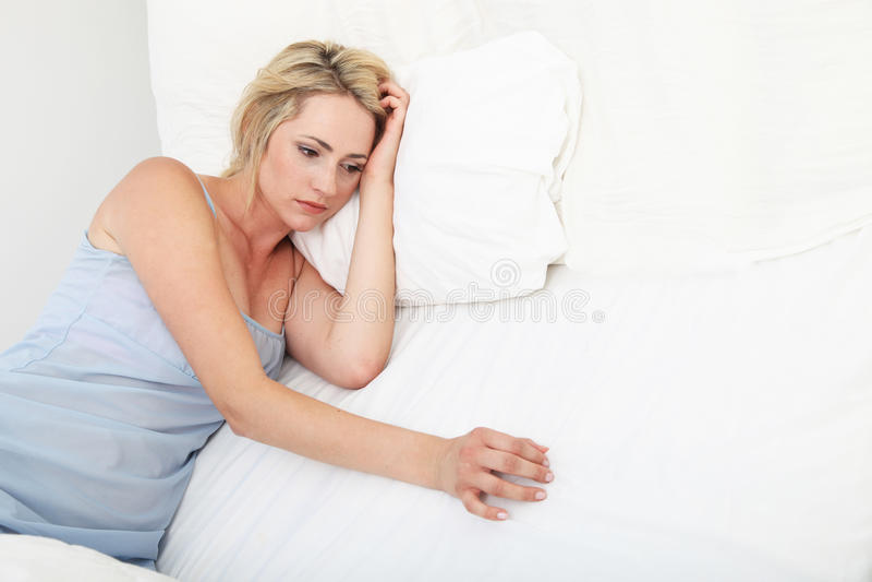 Propped de zieken gedeprimeerde vrouw omhoog op hoofdkussens stock foto