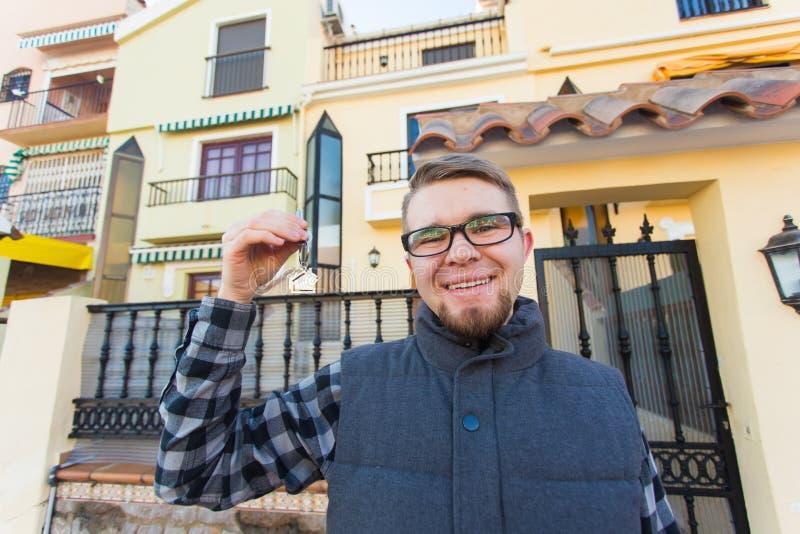 Propriété, propriété, nouvelle maison et concept de personnes - jeune homme avec des clés se tenant en dehors de la nouvelle mais image libre de droits