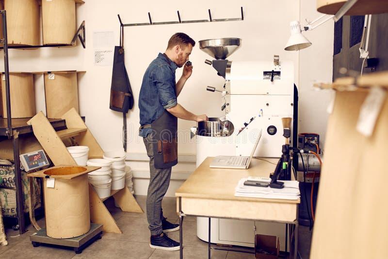 Propriétaire d'un roastery de café vérifiant la qualité de haricots photo stock