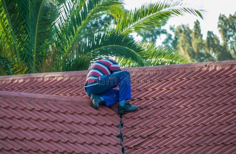Propriétaire d'une maison fixant le toit de sa propriété photographie stock