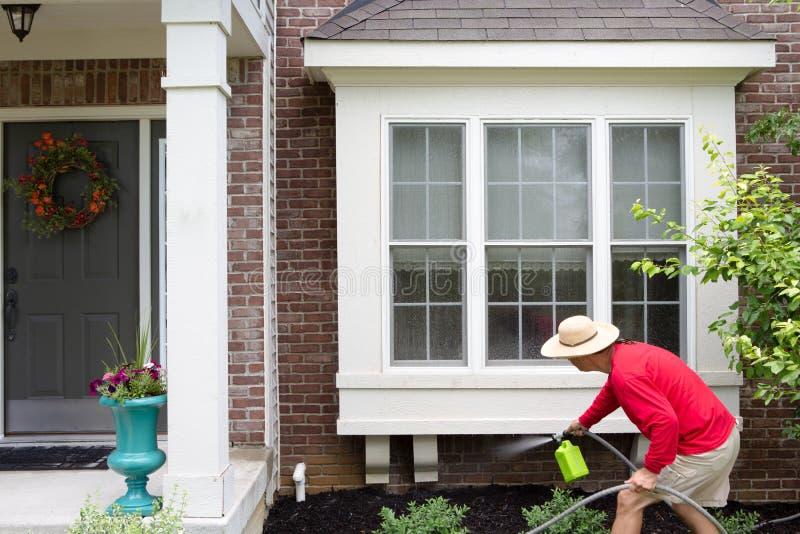 Propriétaire d'une maison lavant vers le bas les fenêtres en saillie photo stock