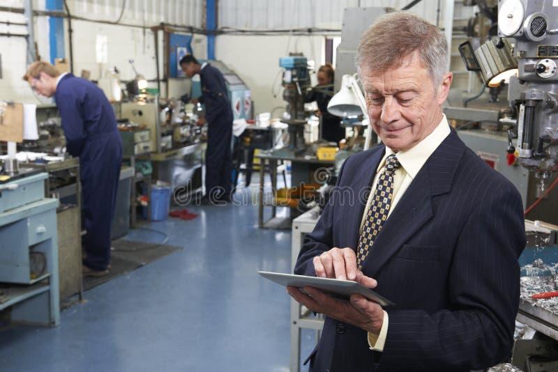 Propriétaire d'usine d'ingénierie utilisant la Tablette de Digital avec le personnel dedans image stock