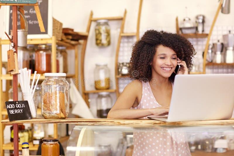 Propriétaire de café de sourire dactylographiant sur un ordinateur portable tout en parlant image stock