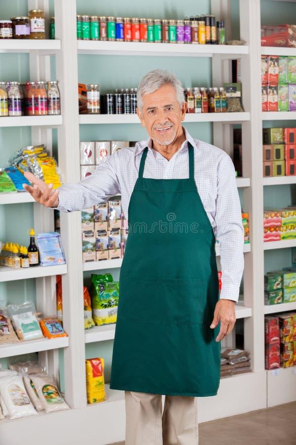Propriétaire de magasin masculin faisant des gestes dans le supermarché image stock
