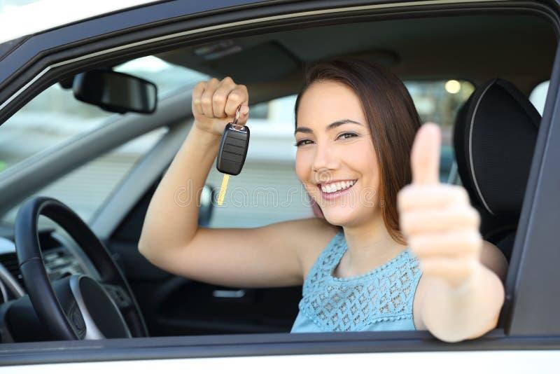Propriétaire de voiture heureux avec une clé et des pouces  image libre de droits