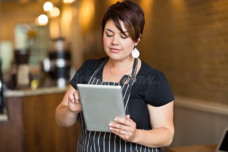 Propriétaire féminin utilisant la Tablette de Digital en café images stock