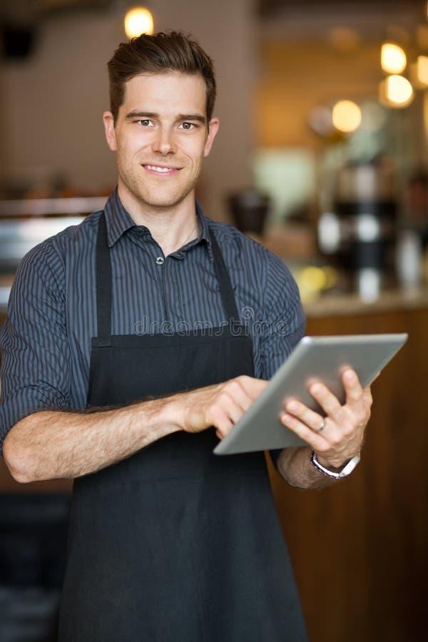 Propriétaire masculin tenant la Tablette de Digital dans le cafétéria image libre de droits