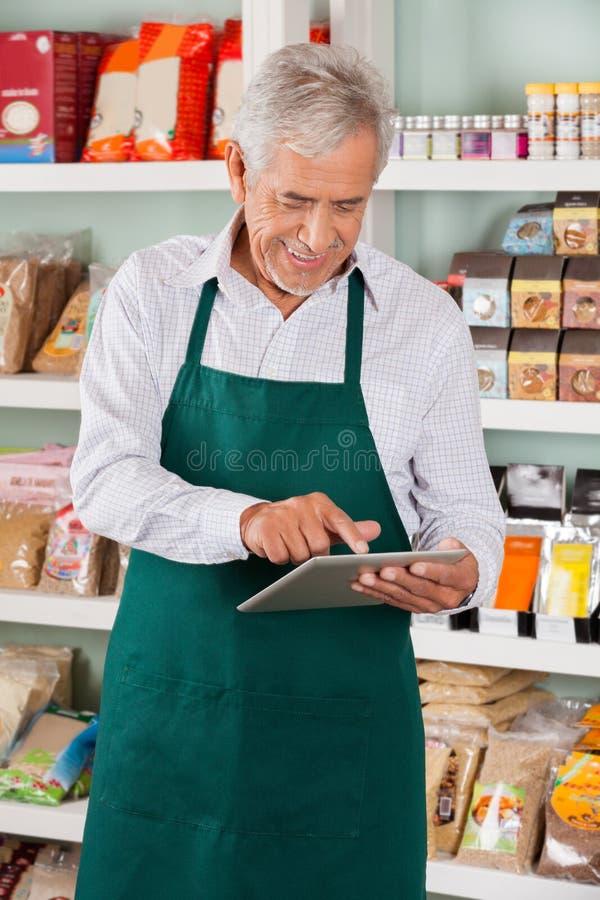 Propriétaire masculin utilisant la Tablette dans le supermarché images libres de droits