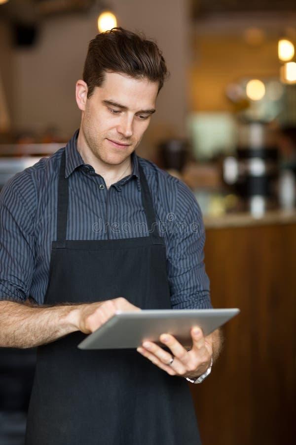 Propriétaire masculin utilisant la Tablette de Digital photo libre de droits
