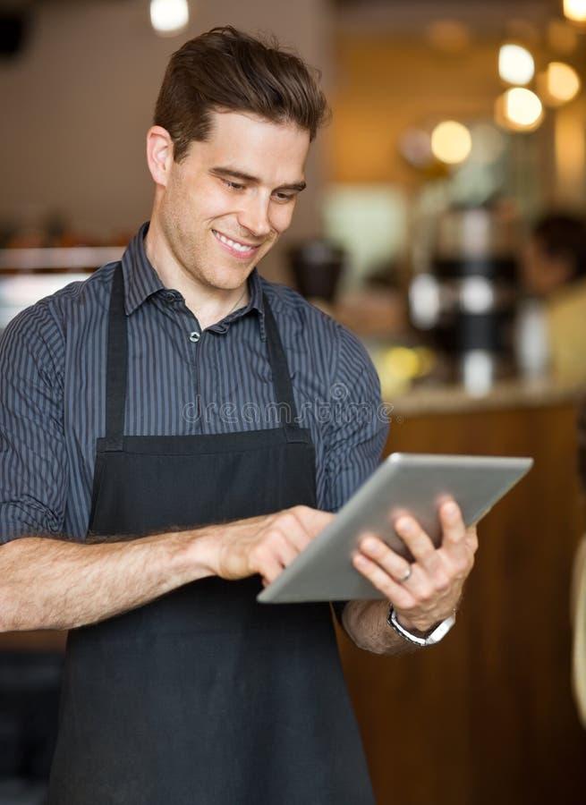 Propriétaire masculin utilisant la Tablette de Digital dans le cafétéria image libre de droits