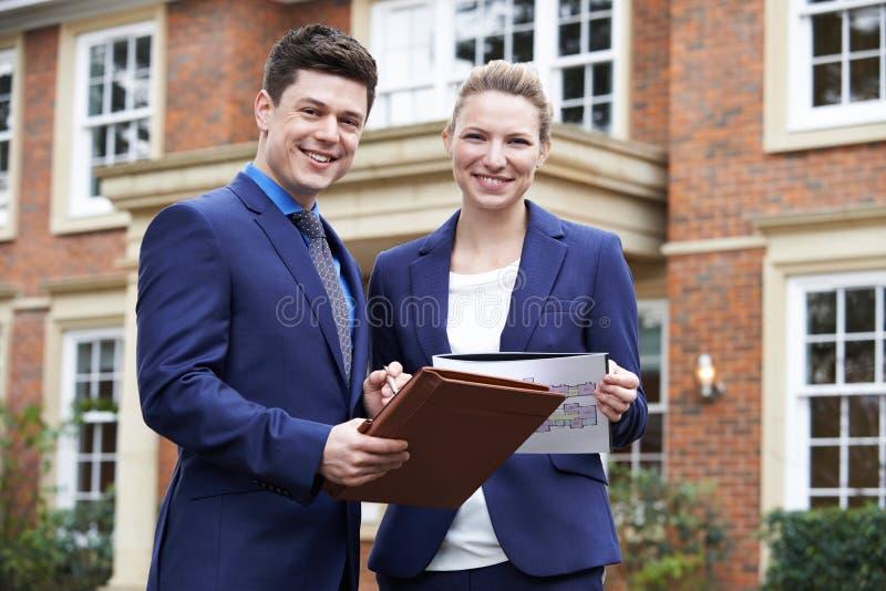 Propriedade residencial da parte externa ereta masculina e fêmea do corretor de imóveis imagens de stock royalty free