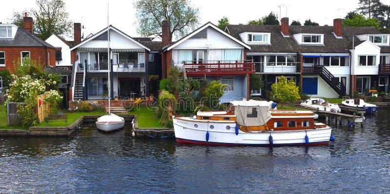 Proprietà di Waterside ed incrociatore antiquato sul fiume Bure a Horning fotografia stock