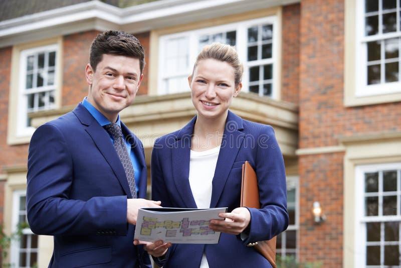 Proprietà residenziale dell'esterno diritto maschio e femminile di agente immobiliare fotografia stock