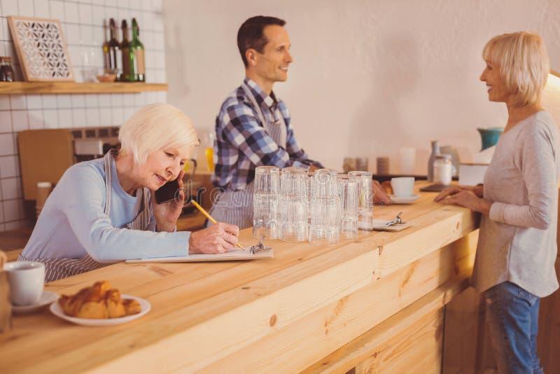 Proprietário agradável do café que coloca a ordem aos fornecedores e que faz anotações foto de stock