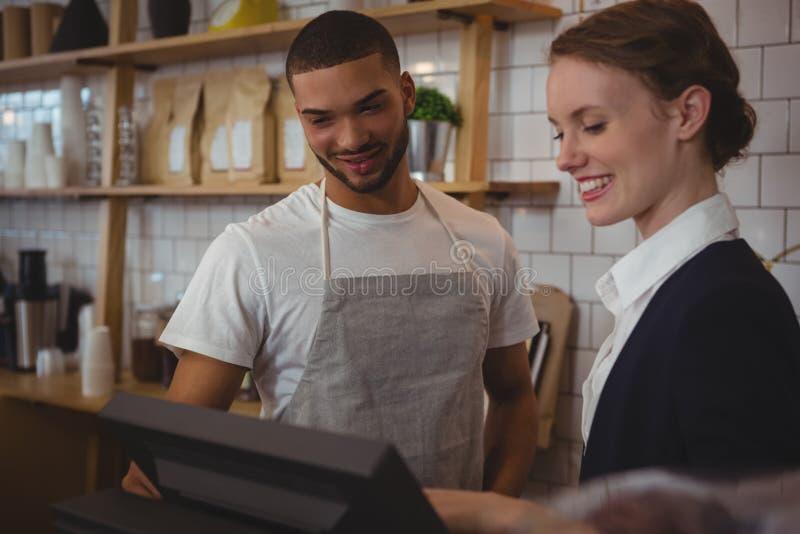 Proprietário com o garçom que olha na caixa registadora no café foto de stock royalty free