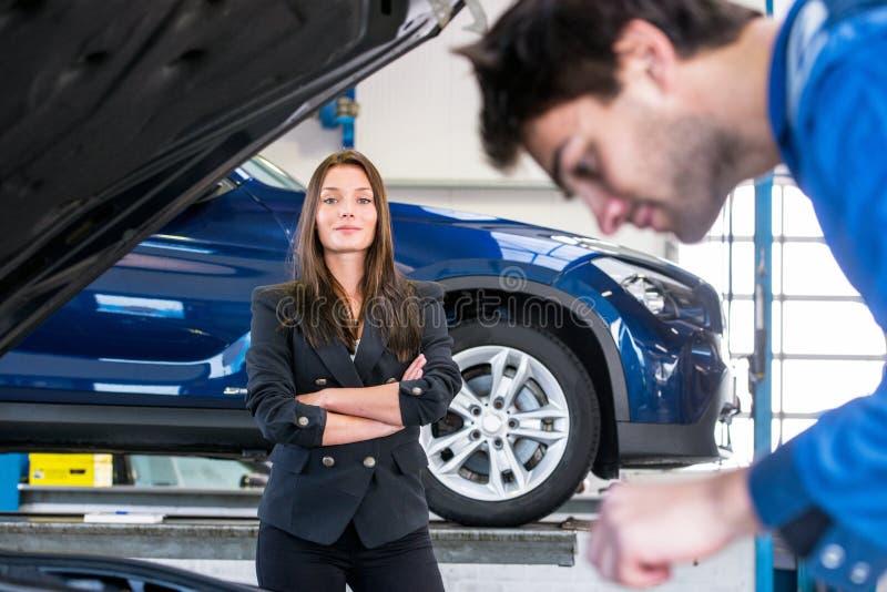 Proprietário de carro que espera em um mecânico para terminar fixar seu carro imagem de stock royalty free