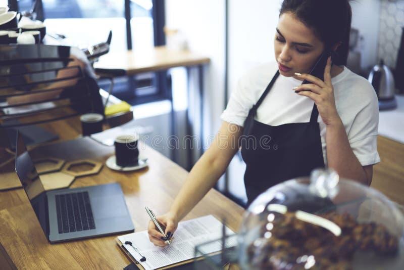 Proprietário de casa do café da mulher que usa o portátil para verificar contabilidades do base de dados, empresário do restauran imagens de stock royalty free