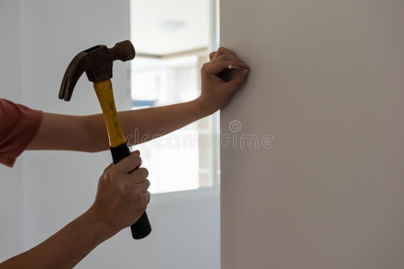 Proprietário de casa masculino que martela um prego na parede branca vazia Conceito da decoração nova da casa imagens de stock