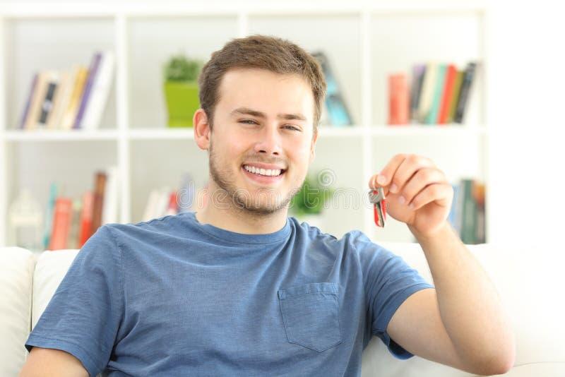Proprietário de casa orgulhoso que guarda chaves da casa imagens de stock royalty free