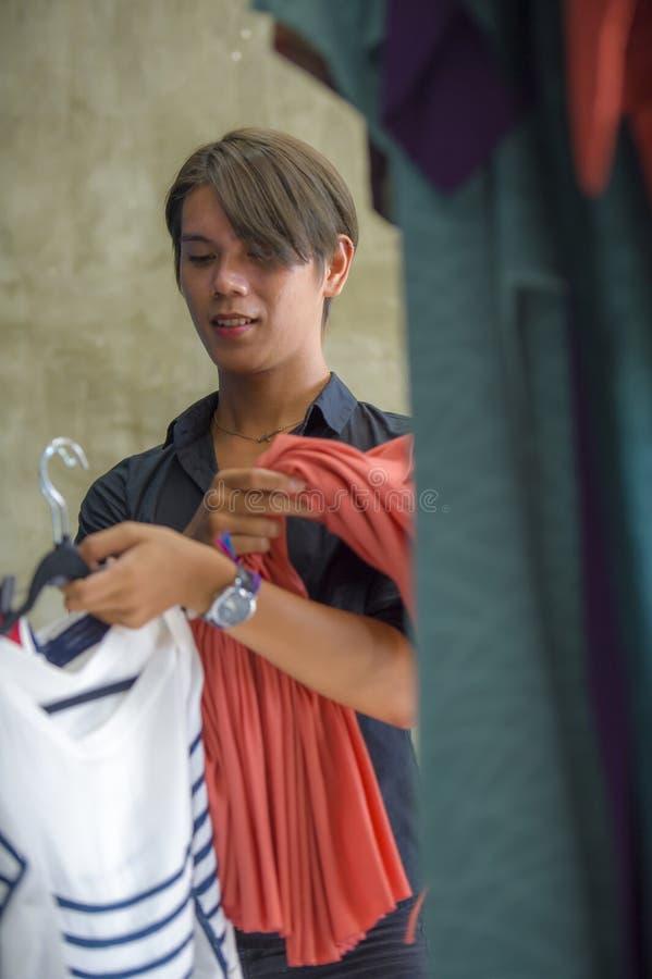 Proprietário de loja novo ou empregado asiático atrativo e fresco da roupa do homem que trabalham no vestuário de organização da  imagens de stock