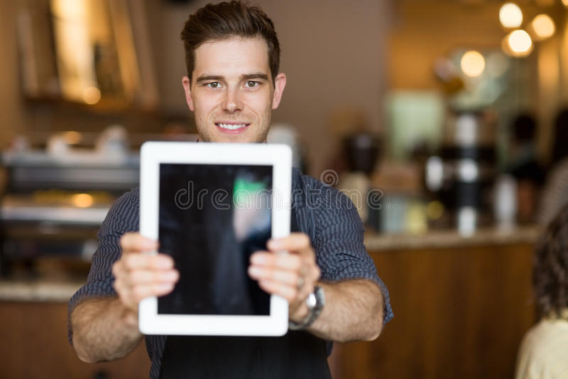 Proprietário do café que guarda a tabuleta de Digitas no restaurante imagem de stock