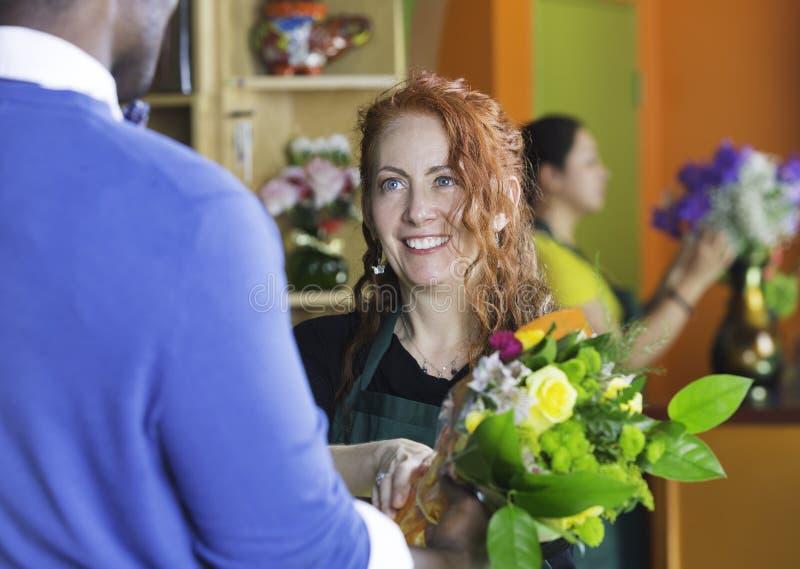 Proprietário e cliente bonitos de florista foto de stock