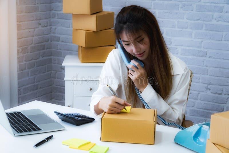 Proprietário empresarial das mulheres que usa o telefone para para confirmar em casa o endereço do cliente e da escrita no escrit imagens de stock