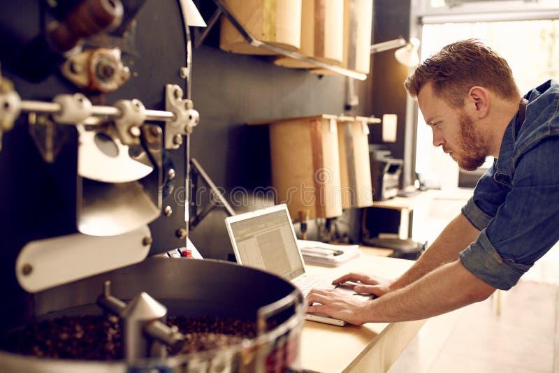 Proprietário empresarial de um roastery do café que verifica seu portátil imagens de stock