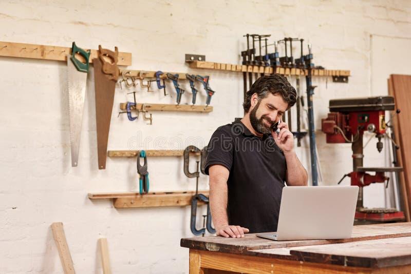 Proprietário empresarial pequeno da carpintaria em seu telefone com um portátil foto de stock