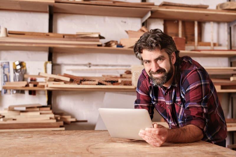 Proprietário empresarial pequeno de sorriso no estúdio da carpintaria com aba digital imagem de stock royalty free