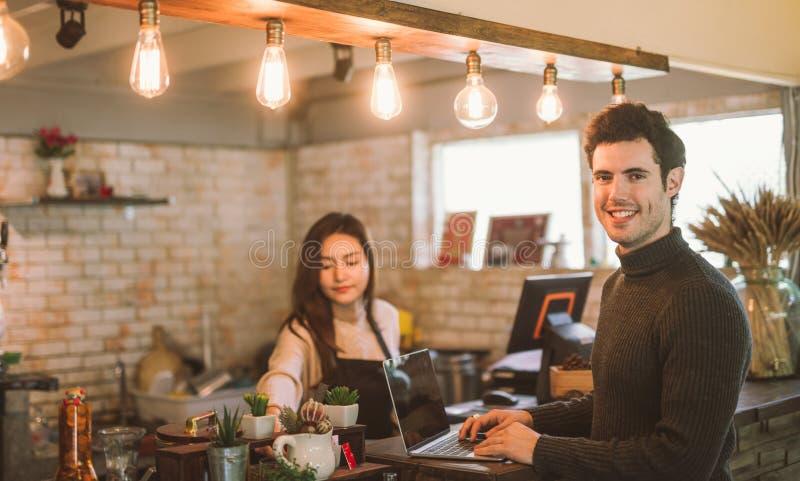 Proprietário empresarial que usa o funcionamento do portátil com o portátil na barra do café moderno imagens de stock royalty free