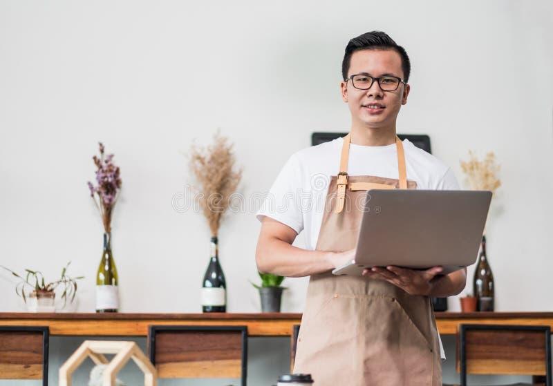 Proprietário masculino asiático do café de Barista que usa o portátil no insi do negócio do café fotos de stock royalty free