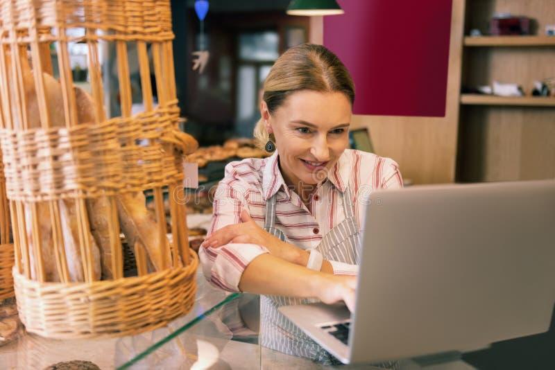 Proprietário próspero da padaria usando seu portátil ao contactar fornecedores imagens de stock royalty free