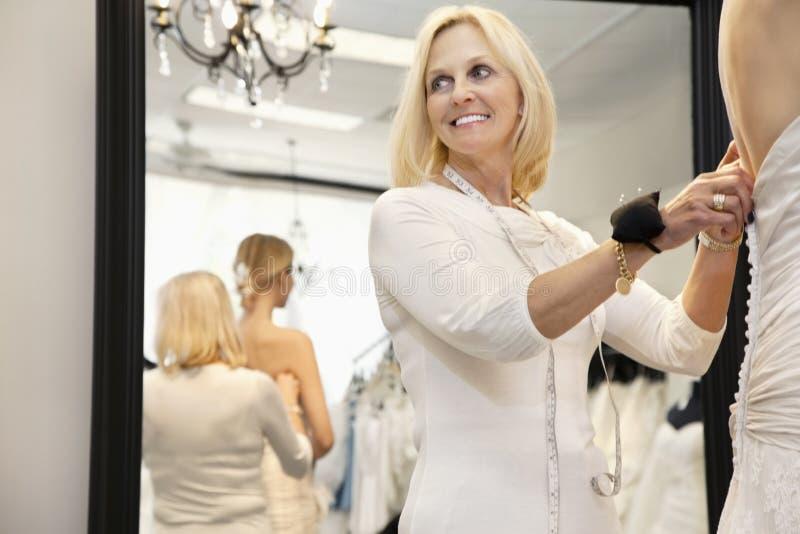 Proprietário superior feliz com a almofada de alfinetes na noiva de ajuda do pulso que obtem vestida imagem de stock