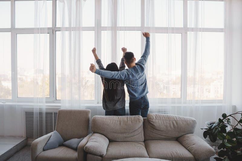 Proprietários lisos novos felizes que olham através da janela imagem de stock