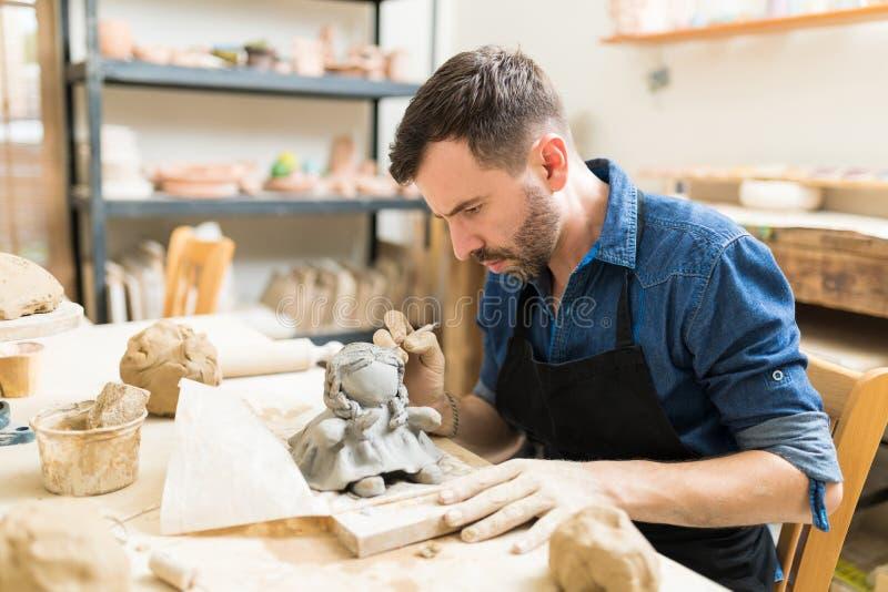 Proprietario che fa il gruppo di lavoro di Clay Sculpture Of Doll In fotografie stock libere da diritti