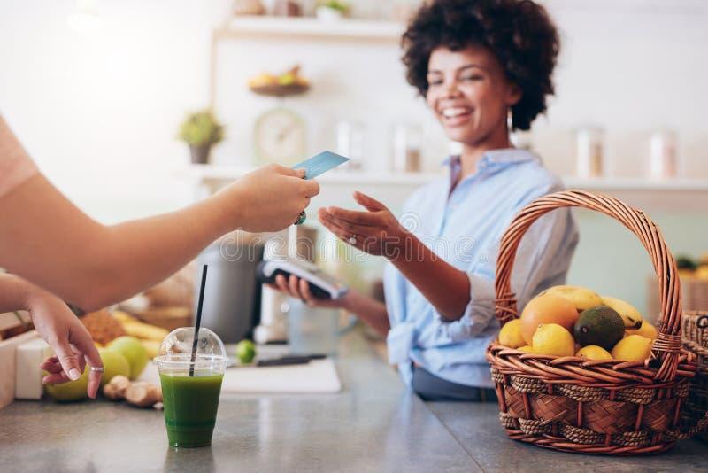 Proprietario della barra di succo che prende pagamento dal cliente immagine stock