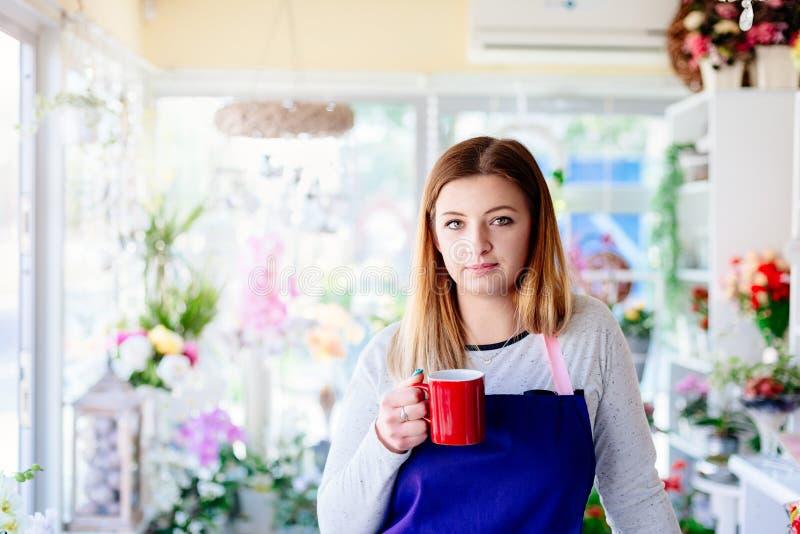 Proprietario della donna del negozio di fiorista che prende una rottura fotografia stock