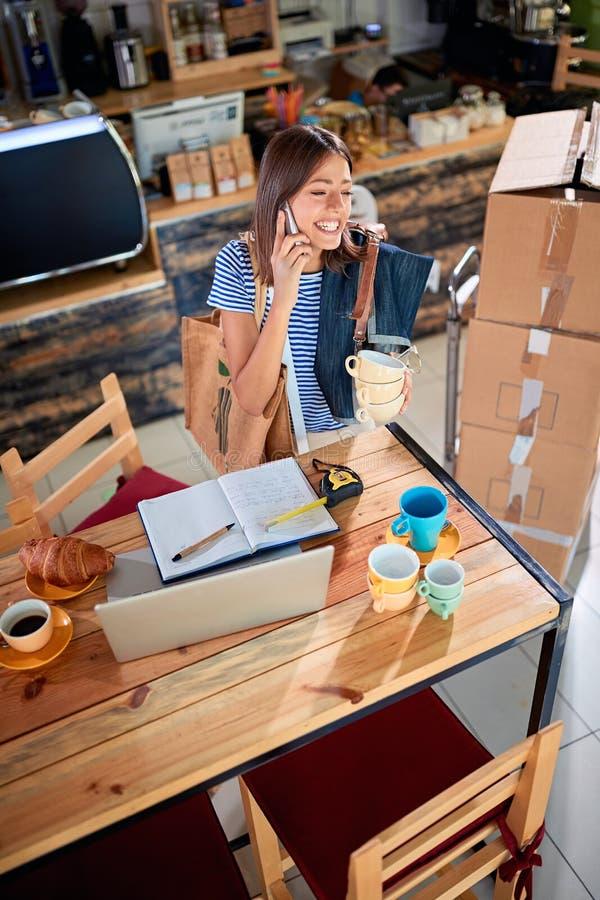 Proprietario della donna di affari che lavora con il computer portatile pronto ad aprire il loro caffè fotografia stock