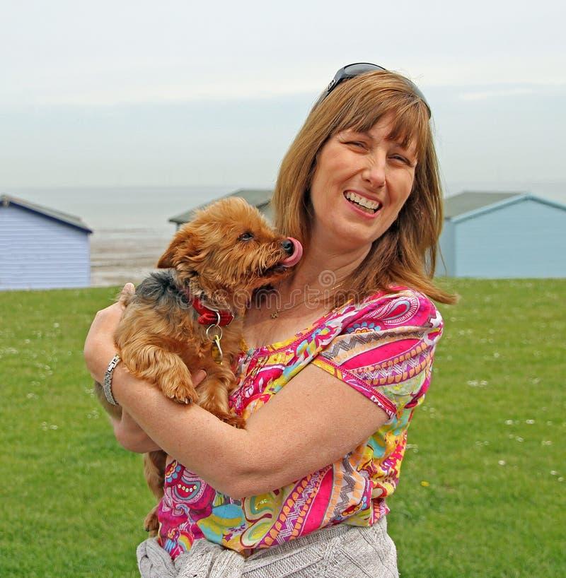 Proprietario e cane dell'animale domestico che leccano per dare a mummia un bacio immagine stock libera da diritti