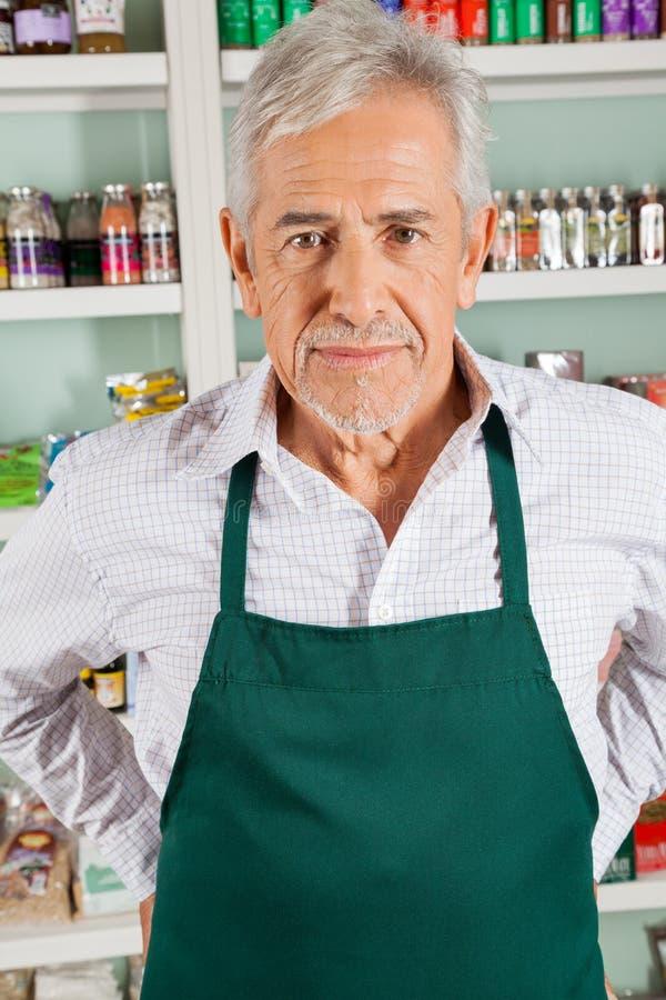 Proprietario maschio senior che sta nella drogheria fotografia stock