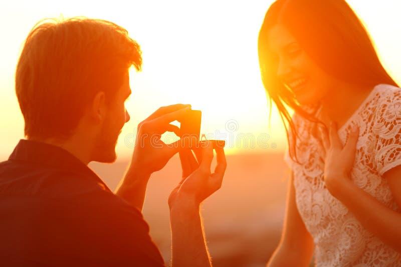 Propuesta de matrimonio acertada en la puesta del sol imagenes de archivo