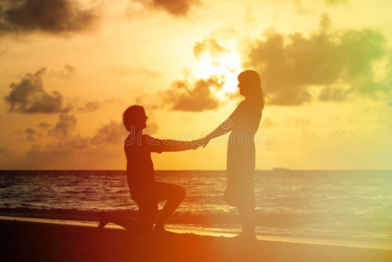 Propuesta de matrimonio en la playa de la puesta del sol imagen de archivo