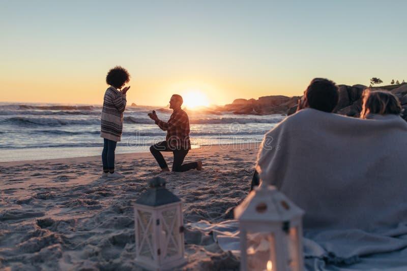Propuesta de matrimonio en la playa de la puesta del sol imagenes de archivo