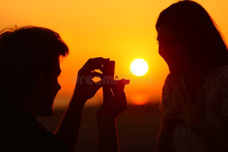 Propuesta de matrimonio en la puesta del sol con el sol en fondo foto de archivo