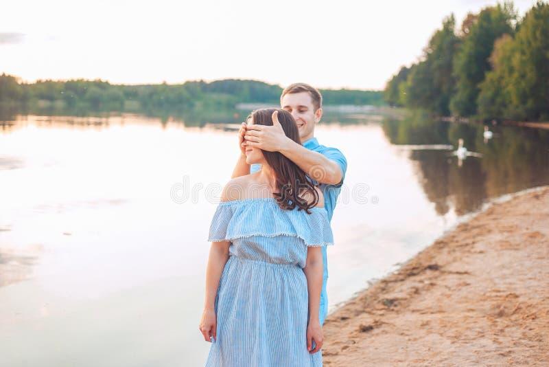 Propuesta de matrimonio en puesta del sol el hombre joven hace una oferta de desposorio a su novia en la playa foto de archivo