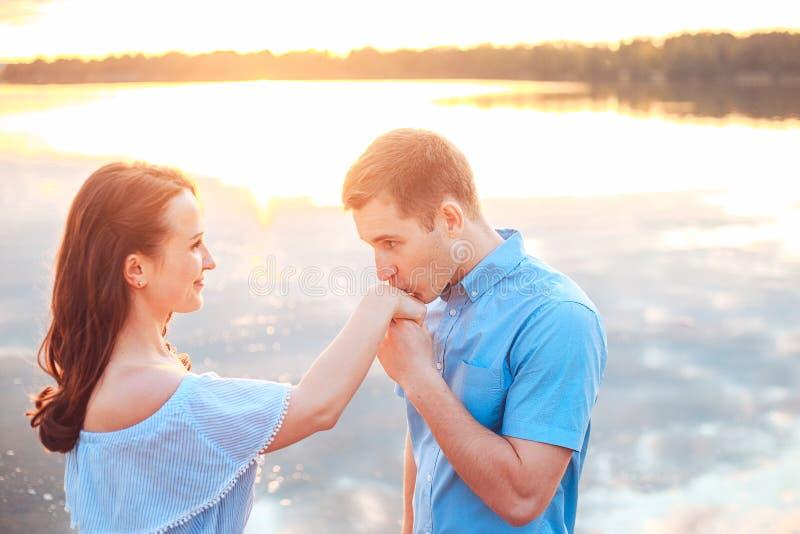 Propuesta de matrimonio en puesta del sol el hombre joven hace una oferta de desposorio a su novia en la playa foto de archivo libre de regalías