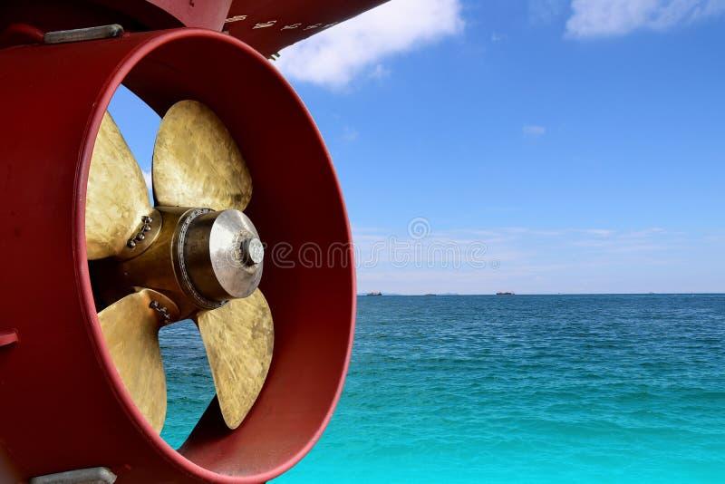 Propulsor en astillero en puerto en fondo azul de agua de mar imagenes de archivo